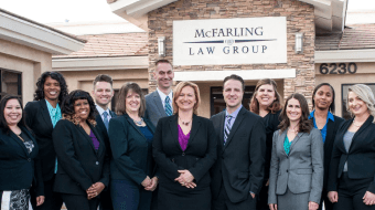 Group of muliple men and women standing, representing McFarling Law Group.