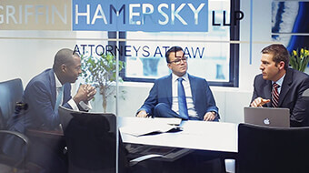 3 men sitting at a conference room table within law firm Griffin Hamersky LLP.